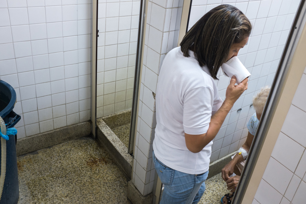 From the series X-Ray. A woman helps an elderly woman to use the deteriorated common toilets in a public. ©Betty Zapata