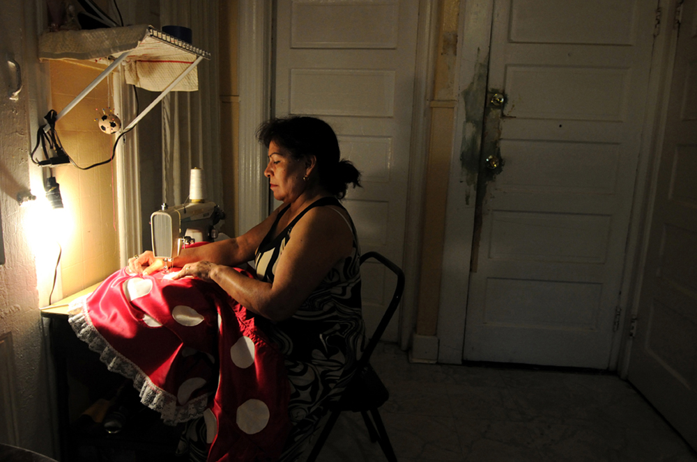 New York, United States. Doña Berta,55,from Mexico repairs her Minnie Mouse costume at her house in New Jersey. 2013 ©Joana Toro.